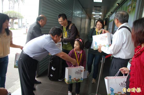 首批從上海包機飛抵水上機場的旅客,受到地方人士熱烈迎接,送見面禮。(記者吳世聰攝)