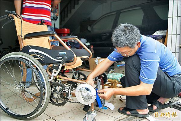 吳昆益自己動手修改傳統輪椅,加裝東西變成可讓母親坐輪椅兼復健雙腳,吳母對成果相當滿意。(記者王秀亭攝)