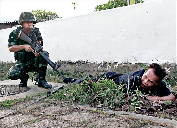 泰國軍方驅離親政府和反政府的示威民眾,圖為一名親政府「紅衫軍」成員遭軍方逮捕。(歐新社)