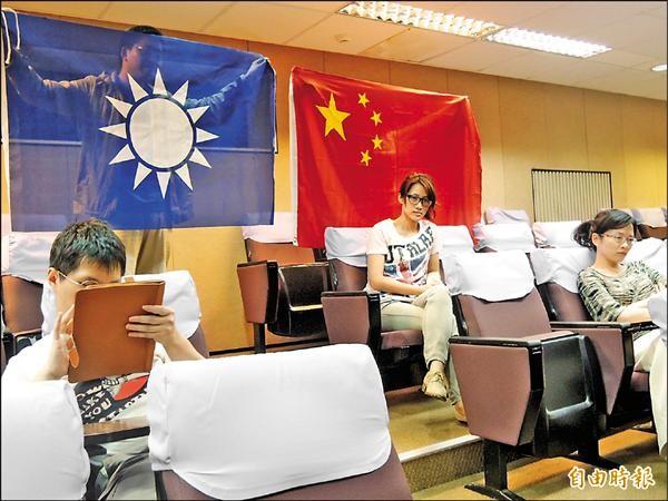 經濟部服務貿易協議列車講座昨上午在成大國際會議廳舉行,學生靜靜舉旗表達反對。(記者洪瑞琴攝)