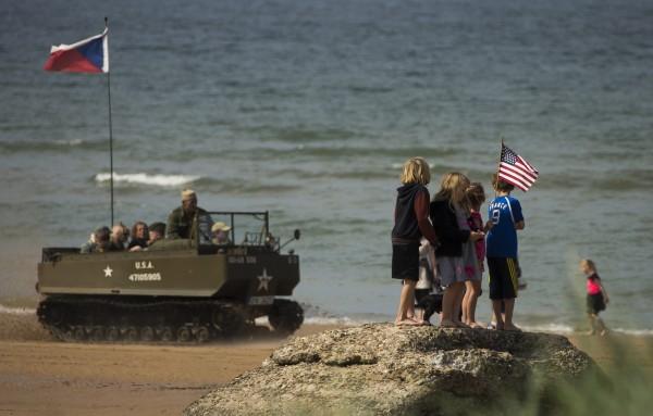 小孩站在二次大戰遺跡奧瑪哈沙灘(Omaha Beach)上。此地約有9300座白色十字架,掉念在此登陸而犧牲的美國軍人。(路透)