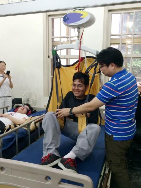 患有脊椎型肌肉萎縮症的周志文,全身肌肉、器官都萎縮。他今天親身體驗由莊錦山發明的自動翻身拍被床。(記者甘芝萁攝)