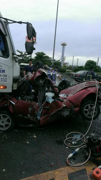 紅色自小客車卡在大貨車底下,駕駛受困,傷勢嚴重。(記者吳俊鋒翻攝)