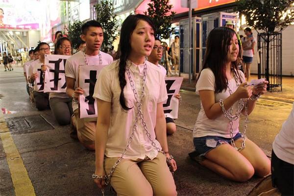 10多名香港大學生6月30日身穿白衣、戴著鐵鍊,在銅鑼灣以七步一跪形式苦行,引起市民圍觀。苦行學生希望喚醒沉默港人,參與七一遊行。(圖取自危城發聲捨我其誰臉書)