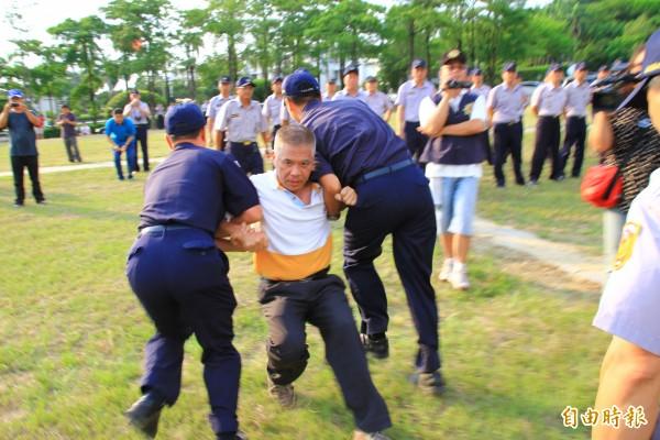 「美國台灣政府」主席蔡明法(中)被警方強制架離921紀念公園。(記者佟振國攝)