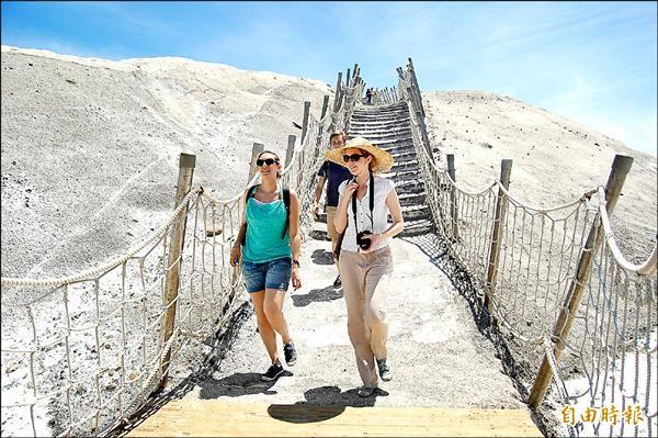 觀光客可循著鹽山表面開鑿的鹽階登頂,部分外國觀光客對鹽山變黑,覺得很奇怪。(記者楊金城攝)