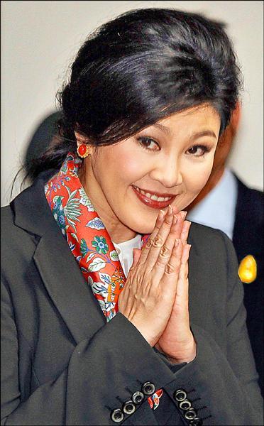 前泰國總理盈拉獲准出境,圖為五月間她在曼谷一場記者會上,比出傳統問候手勢的檔案照。(路透)