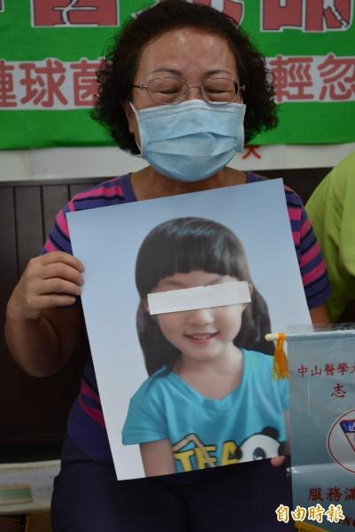 王姓女童阿嬤拿著孫女生前照片,哽咽表示沒想到孫女會死在最相信的醫院。(記者陳建志攝)