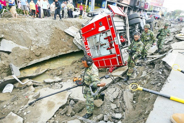 Rescue personnel survey the wreckage after a series of explosions in Greater Kaohsiung early yesterday. Photo: Toby Chang, Reuters