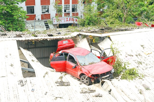 A car is seen in Greater Kaohsiung yesterday after it was blown onto the roof of a three story building due to the strength of a series of gas explosions that shook the municipality from late Thursday night to early yesterday morning.
