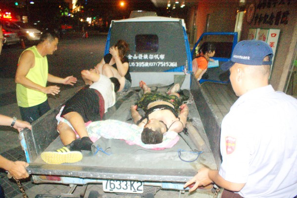 People injured in gas explosions in Greater Kaohsiung are put onto the back of a small truck yesterday due to a lack of ambulances.