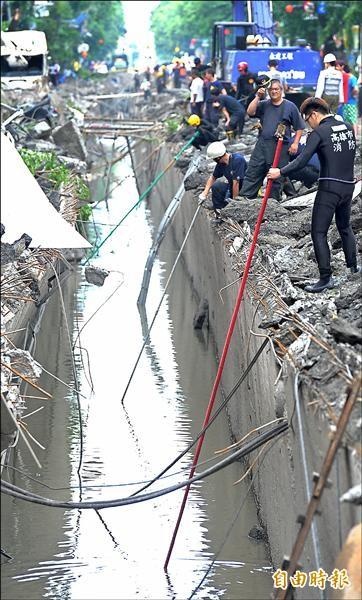 消防人員手持竹竿,在下水道找尋有無落水者。(記者黃志源攝)