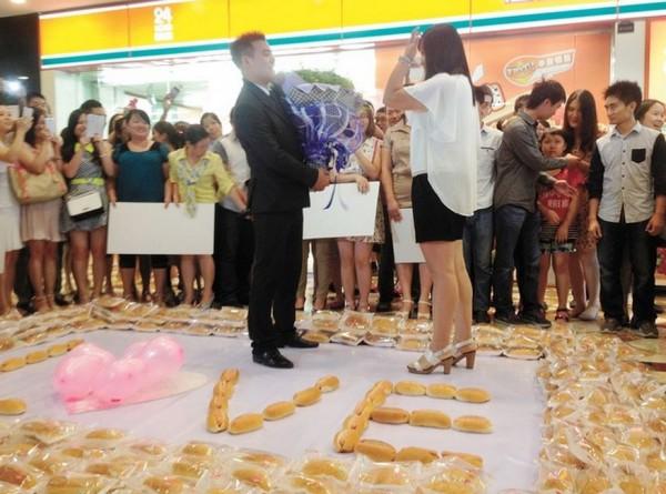 中國四川1名男子準備1001個熱狗堡向女友求婚,女友在眾人簇擁下點頭答應。(圖片擷取自《人民網》)