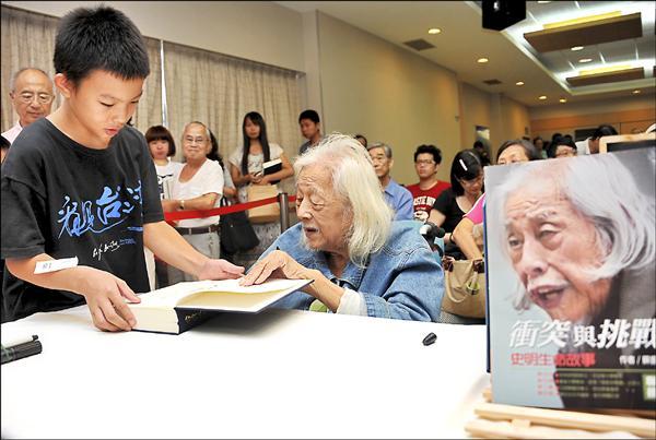 台獨大老史明昨舉辦人生首場簽書會,幫小粉絲簽書。(記者陳奕全攝)