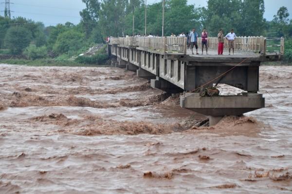 印度、巴基斯坦暴雨成災,許多橋梁被洪水沖毀,村民還冒險在橋上觀看對岸。(法新社)