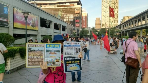 法輪功成員拿著圖片,沉默控訴中國共產黨的殘酷打壓。(資料照,記者陳彥鈞攝)