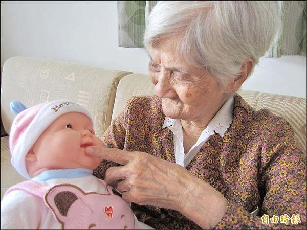 86歲的失智阿嬤抱著洋娃娃,整個人變得溫柔又安詳。(記者廖淑玲攝)