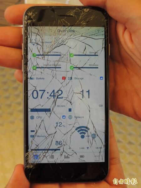 將愛瘋6鏡面朝下「摔機」,螢幕嚴重碎裂,但手機功能正常。(記者洪定宏攝)