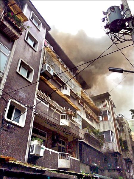 新北市永和區一公寓的加蓋鐵皮屋冒濃煙,消防局第7大隊迅速趕至火場,10分鐘內撲滅火勢。(記者吳張鴻翻攝)
