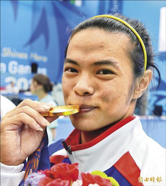 仁川亞運女子舉重53公斤級,許淑淨以挺舉132公斤、總和233公斤雙破世界紀錄,為台灣代表團奪下本屆首面金牌,賽後她開心地咬金牌,品嚐勝利滋味。(特派記者王藝菘攝)