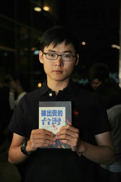 來自高雄的18歲顏姓學生,朝馬英九丟擲被出賣的台灣一書。(記者劉信德攝)