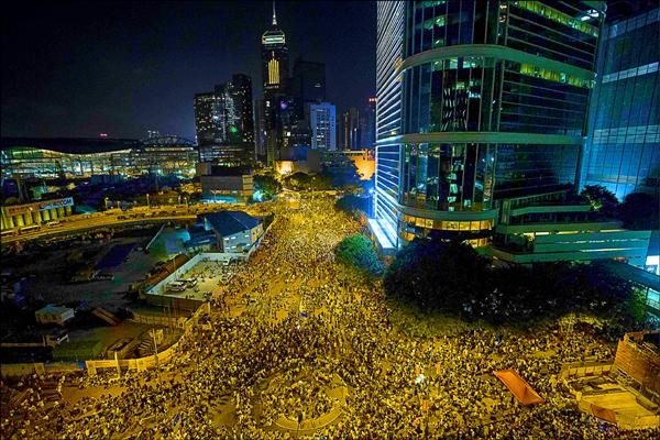 大批民眾27日晚間湧入政府總部周圍聲援爭取真普選的示威群眾,至午夜人潮未散,6萬人通宵留守。(路透)