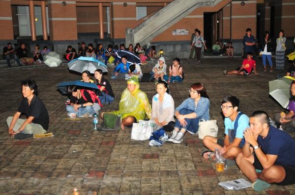 東華、慈濟支持香港佔中行動的學生席地而坐,雖然下雨仍不散場,穿著雨衣、撐傘給香港朋友溫暖支持。(記者花孟璟攝)