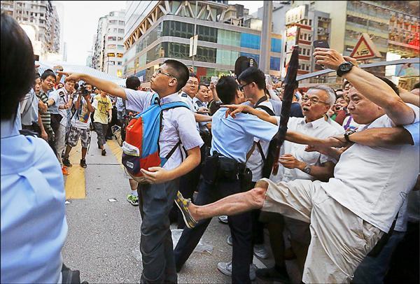 ▲一名旺角佔中人士(背包掛胸前者)遭一名反佔中者踢腳偷襲。(路透)