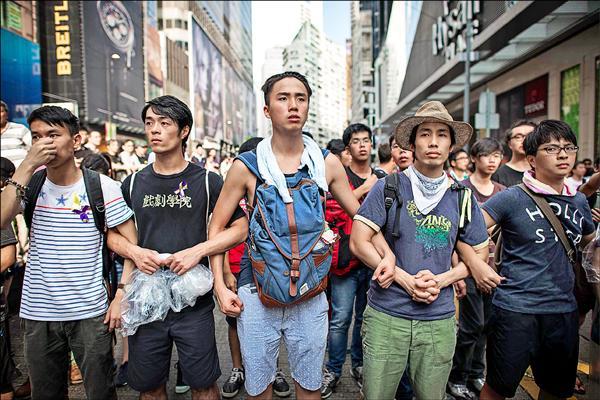 佔中與反佔中群眾三日在旺角與銅鑼灣等集會現場爆發衝突,有大批反佔中人士毆打佔中人士。圖為旺角佔中人士組成人牆,阻擋反佔中群眾衝入集會區。(法新社)