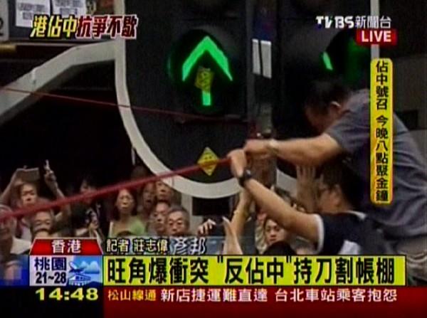 TVBS報導,有男子掏刀嘗試拆下固定帳棚的繩子,隨後被群眾制服。(圖擷取自TVBS)