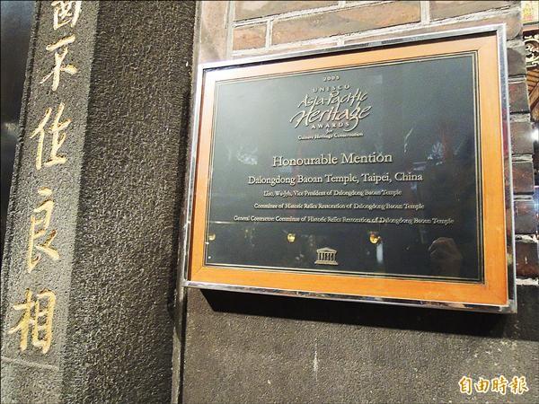 大龍峒保安宮於十一年前就獲「聯合國教科文組織」頒發亞太文化資產保存獎。圖為聯合國頒發的獎碑,今懸掛正殿柱上。(記者葉冠妤攝)