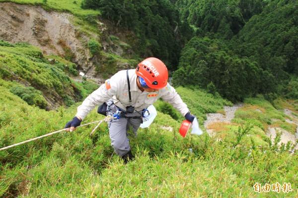 神鷹山區搜救隊員在合歡山淨山,利用繩索冒險垂降至筆直深谷,撿拾遊客棄置的垃圾。(記者佟振國攝)