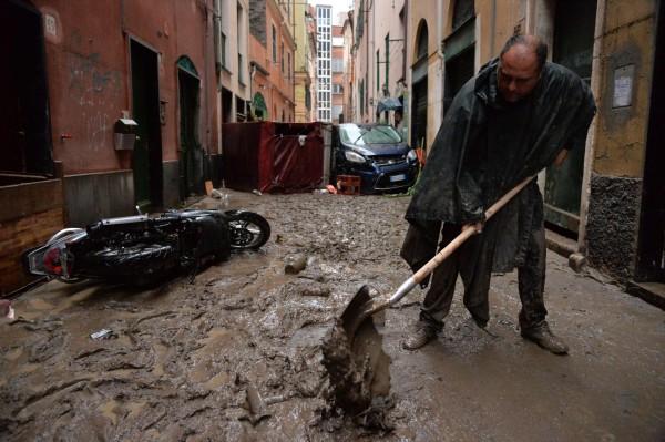 洪水肆虐讓熱那亞市成為汪洋澤國,街道上的櫥窗泥濘一片,汽車也統統成了泡水車,當局出動大批清潔人員打掃。(歐新社)
