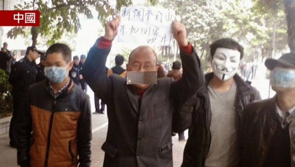 參與「口罩革命」的中國民眾高舉牌子,「新聞不自由,不如回家吹牛!」(圖取自香港蘋果日報臉書)