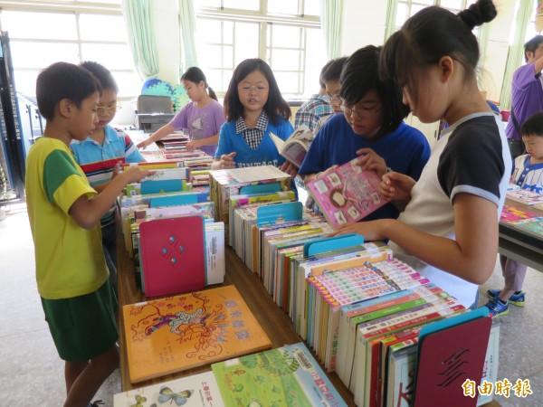 集集鎮圖巡迴書展來到隘寮國小,學生們開心找尋喜歡的書籍。(記者劉濱銓攝)