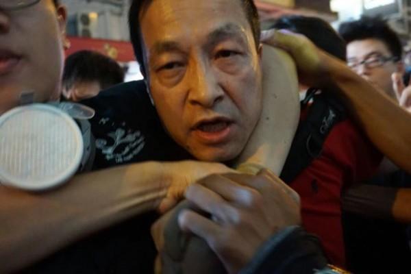涉嫌丟擲易燃物的男子遭附近民眾制伏。(擷取自香港獨立媒體網)