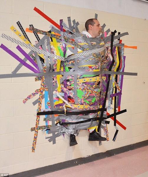 學生順利賣出1萬1千張小鎮的秋季節票券,校長實現承諾,讓自己被學生黏在牆上。(圖取自每日郵報)