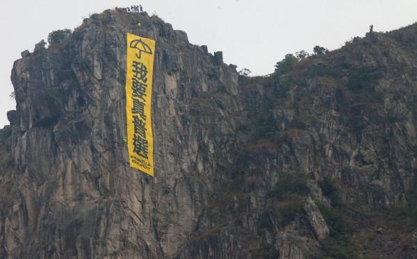 一群挺香港佔中的攀岩好手,今天上午攀登香港獅子山,在山頭掛上大型布條。(歐新社)