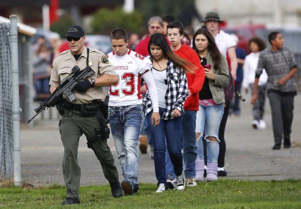 馬里斯維爾皮楚克高中學生在警方保護下,被帶至安全區域避難。(圖擷自《西雅圖時報》)