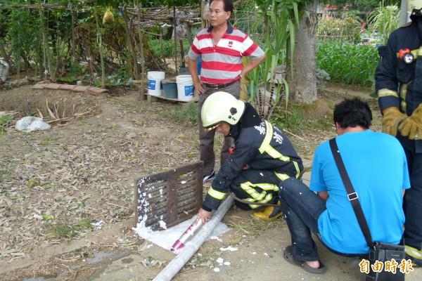 消防隊員往水溝噴灑泡沫壓制汽油味。(記者蔡宗勳攝)
