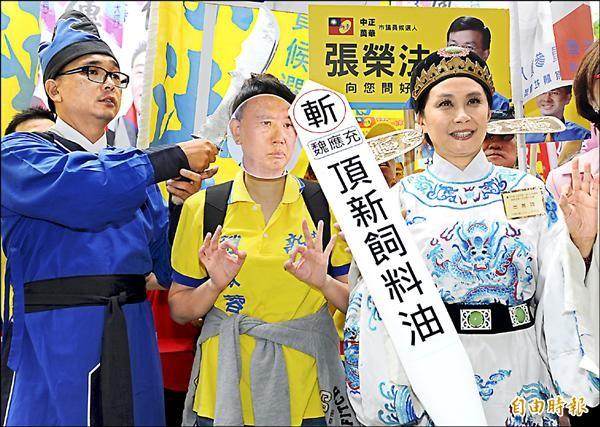 新黨台北市議員候選人趙家蓉(右)趕搭黑心油話題,一身官服要將魏應充問斬。(記者張嘉明攝)
