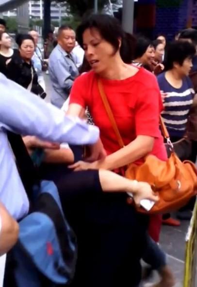 有現場民眾恰好將中國配偶張秀葉(紅衣者)毆打蔡姓婦人的畫面給拍攝下來。(圖擷取自大紀元時報)