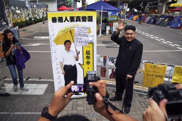 霍華德特地模仿金正恩到香港佔中現場,還站在習近平看板旁讓大家拍照。(路透)