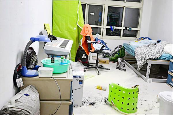 學生的寢室,滿地皆是乾式滅火器粉劑,綠色的洗衣桶被燒掉一半。(家長提供)