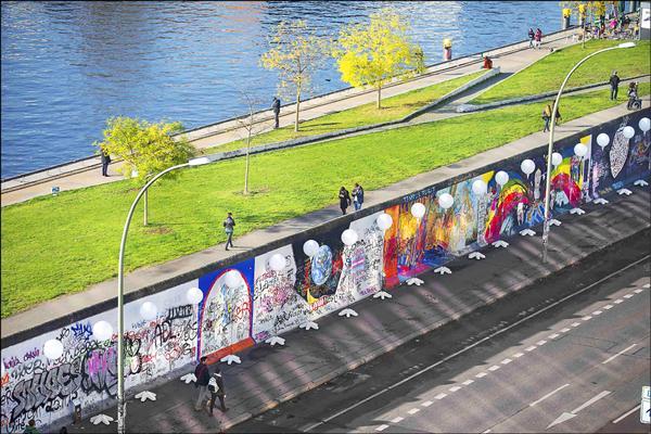 圖為德國人7日走過柏林圍牆舊址沿線擺設的氣球燈牆。(路透)