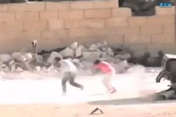 敘利亞媒體上傳的一段影片中,可見一名男童在槍林彈雨中,捨命救出另一名受困於戰火中的女童。(圖擷取自YouTube)