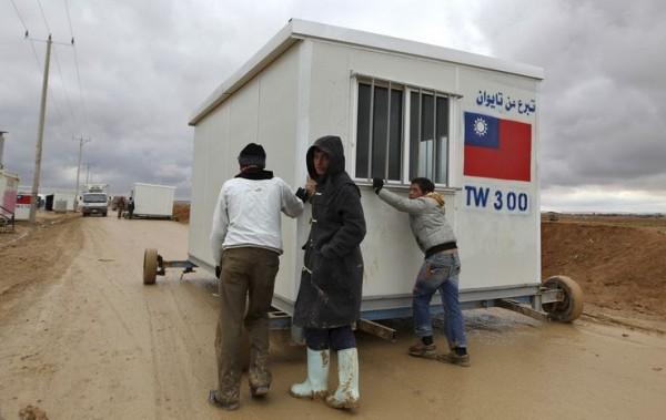 敘利亞難民推著由台灣援助的物資前往營地。(路透)