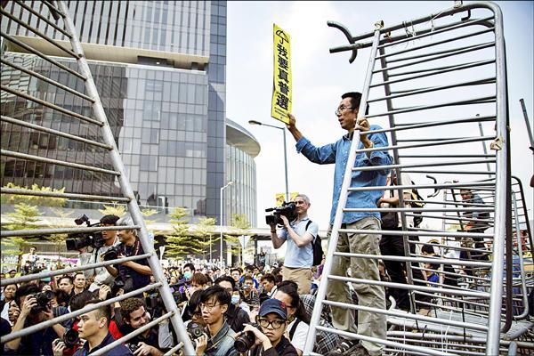 一名示威者在金鐘中信大廈外手持「我要真普選」標語,站在豎立的柵欄上。(彭博)