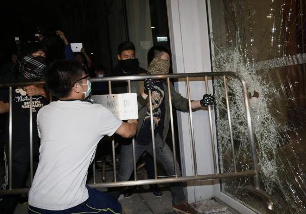 香港數十名網友昨晚號召群眾衝撞立法會,強行打破立法會玻璃,並與警方發生衝突,讓佔中行動勢力憂心訴求變調。(路透)