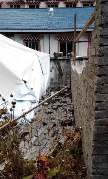 中國四川省康定縣日前生地震,地震過後房屋磚牆倒塌的景象。(法新社)